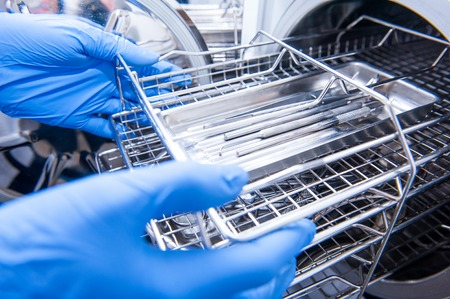 Dentist assistant's hands get out sterilizing medical instruments from autoclave. Selective focus
