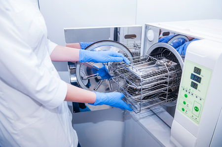 Dentist assistants hands get out sterilizing medical instruments from autoclave. Selective focus