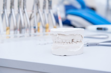orthodontist: Close up dental gypsum jaw model on the background of orthodontist set of clamps and pliers. Selective focus Stock Photo