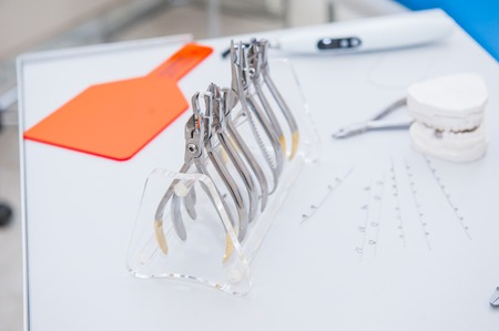 Close up Orthodontist Dental set of clamps and pliers and other tools on the working table surface