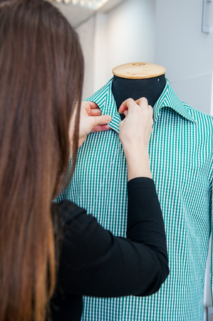 Female seamstress prepares a mans shirt to the fitting. Selective focus