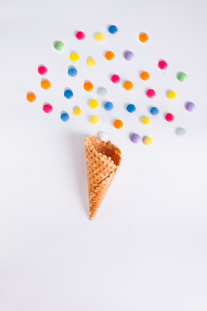 happieness: Colorful candies bang from ice cream cone on the white background. Place for lettering. Top view, flat lay. selective focus.