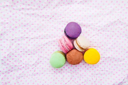 Multicolored cake macaron or macaroon in the triangle form on the white with pink peas background. Top view. Free space for text Stock Photo