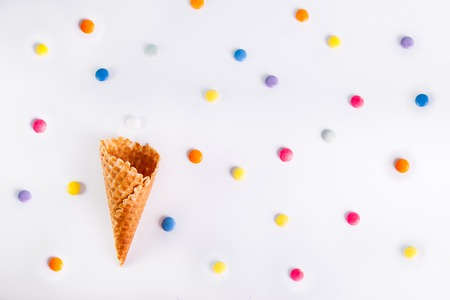 happieness: White Background with colorful candies and empty ice cream cone. Top view, flat lay. selective focus