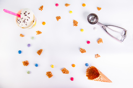 impression: White Background with colorful candies, pieces of waffles, ice cream and empty ice cream cone. Place for lettering. Top view, flat lay. selective focus.