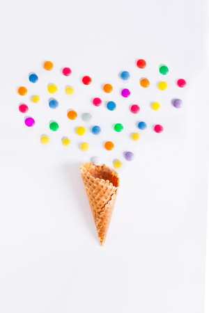 Colorful candies in the shape of a heart and ice cream cone on the white background. Place for lettering. Top view, flat lay. selective focus. Stock Photo