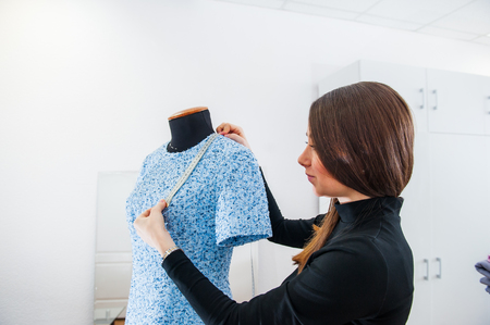 Female seamstress prepares dress to the fitting and takes measurements. Selective focus Stock Photo
