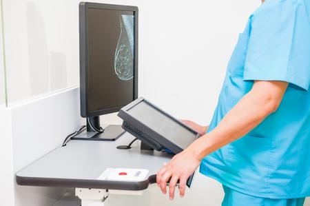 Arts die mammamieopname van borsten van een vrouwelijke patiënt op de monitor bekijkt. Selectieve aandacht