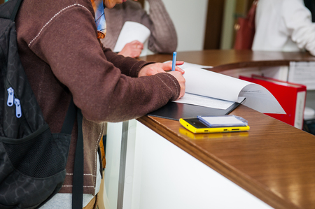 details: Close up of a woman hand writing or signing in a document on a reception zone of clinic. Selective focus
