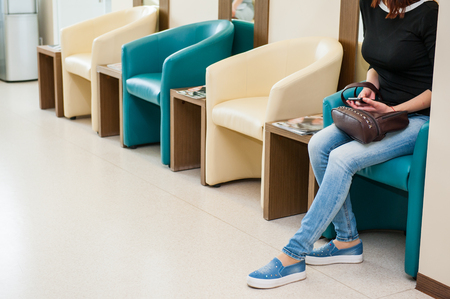 office furniture: Young girl sitting in waiting room on the one of row of blue and ivory chairs in hall. Selective focus. Medicine, business concept