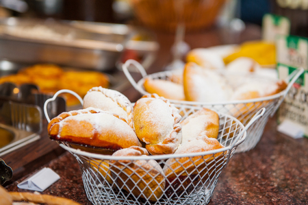 Close up baskets with freshly baked pastry goods on display in cafeteria shop. Selective focus
