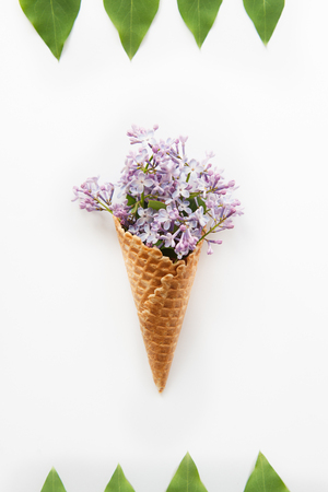 invitando: Card with Close up Bouquet of purple lilac flowers in the waffle cone and frame of raws of green leafs on the white background. Top view. Flat lay. Space for text. Selective focus