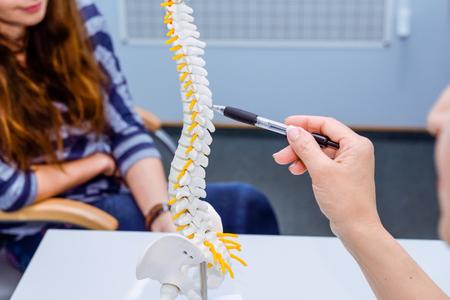 Closeup femme médecin pointant sur le modèle de la colonne vertébrale et expliquant sa patiente son problème. Concept de soins de santé