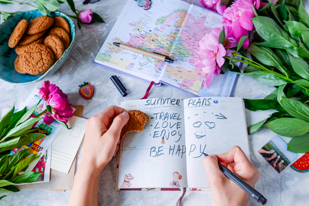 hapiness: Female Summer planning holiday background with notebook, envelopes and postcards, peonies and cookies. Vacation planning concept. Top view, selective focus