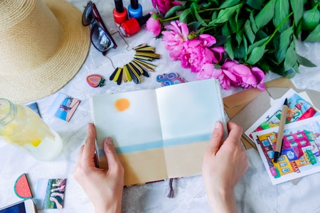 hapiness: Summer plan background - female hands with notebook and lemonade surrounded with details: hat, sunglasses, envelopes, postcards, peonies. Vacation planning concept. Top view, selective focus. Stock Photo