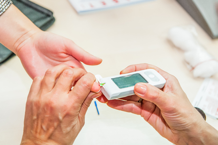 Close up process of mobile diabetes testing for sugar level. Normal blood sugar level. Doctor takes blood for test. Medical process, modern healthcare concept Stock Photo