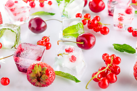 refrigerate: Close up ice cubes with fresh berries among not frozen cherry, strawberry and mint leafs on the white background. Selective focus.