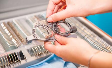 De vrouwelijke handen van de opticien kiezen lenzen uit de set corrigerende lens die op de platen van de vorm wijst: concaaf, convex, cilindrisch. Abstracte achtergrond van oogheelkundeconcept. Selectieve aandacht