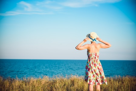 Summer portrait of young pretty woman in a straw hat and dress standing backwards in the grass and looking to the sea. Girl enjoy nature sea paradise and fresh air at wonderful summer vacation. Stock Photo