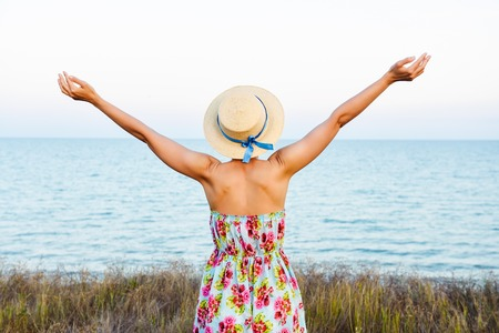 Young woman arms raised up to sky, celebrating freedom. Positive emotions feeling life perception success, peace of mind concept. Free Happy girl in summer meadow enjoying sea skyline. Text space. Фото со стока