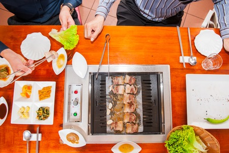 Process of cooking Korean barbecue raw pork on the tabletop grill in restaurant. Selective focus. close up Stock Photo