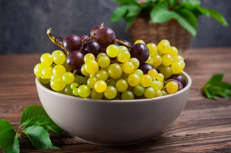 Close up bowl of various grapes: red, white and black berries on the dark wooden table with wicker basket with leaves in the background . Selective focus Stock Photo