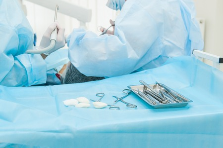 Close up dental surgery process - Implantation. Dentist surgeon with assistant in modern clinic. Stomatology and health care concept. selective focus. Space for text. Foto de archivo