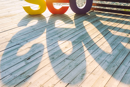 html: The word SEO by large colored letters creating a shadow on the wooden terrace on the river bank. Sun backlight. Selective focus. Space for text. Stock Photo