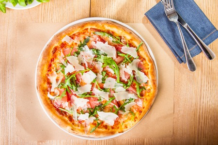 Top view Pizza with prosciutto, parma ham, arugula and parmesan on served wooden restaurant table. Italian cuisine. Selective focus, copy space Stock Photo