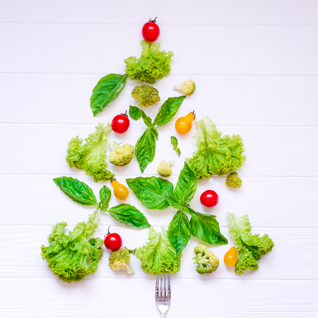 Healthy new year concept - Collection of fresh organic vegetables and greeens in form of christmas tree on white wooden background. Top view. Selective focus. space for text.