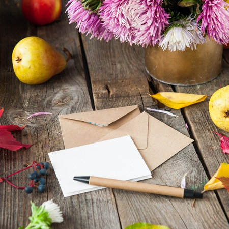 Thanksgiving background with seasonal fruits, flowers, greeting card and few craft envelopes on a rustic wooden table. Autumn harvest concept. Confession in feelings. Selective focus, Space for text