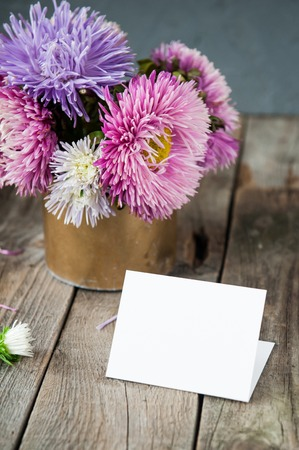 Multicolor aster flowers bouquet, blank white greeting card on rustic wooden table and dark grey background. Postcard mock up. Autumn flowers. Selective focus. Space for text