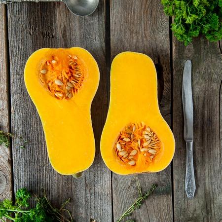Bovenaanzicht Snij rijpe oranje pompoen met zaden op de rustieke houten tafel. Vegetarisch, veganistisch, gezonde voeding. Herfst oogst concept. Selectieve aandacht. Ruimte voor tekst, vierkante foto.