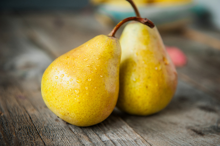 Autumn harvest concept -a couple of Fresh ripe organic yellow pears with water drops on rustic wooden table, dark stone background. Vegetarian, vegan, healthy diet food. Selective focus. Reklamní fotografie