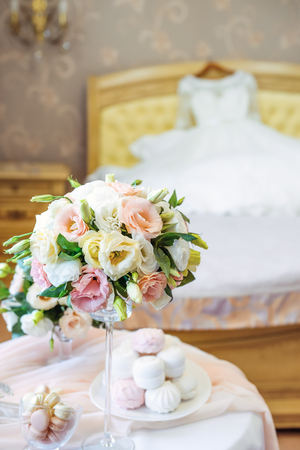 Interior room: Table with brides details: bouquet of eustoma flowers, jewelery, perfumes and marshmallow and macaroon sweets with blurred Wedding dress lying on the bed on the background. Selective focus.