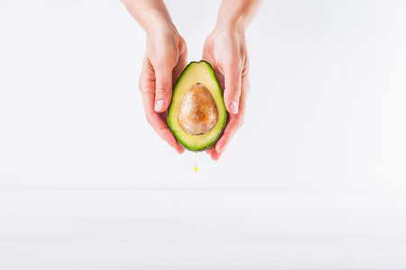 elasticidad: Fresh avocado with oil drop in female hands on the white background isolated. Healthy, natural beauty concept. Front view. Space for text Foto de archivo