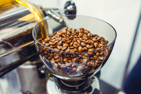Fresh roasted coffee beans in coffe grinder. Selective focus. Stock Photo
