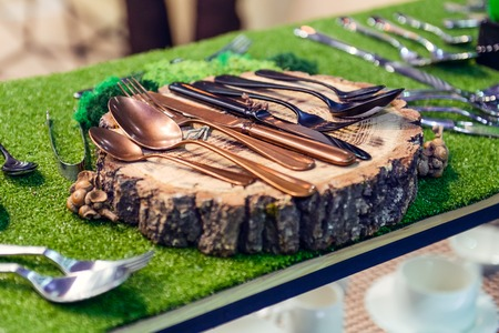 Exhibition of unusual cooper and black Cutlery set with Fork, Knife and Spoon on wooden stand on the green grass background. Selective focus.