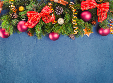 Dark blue christmas background with fir branches and new year decor and toys on a slate or stone backdrop. Top view with copy space. Selective focus. Stock Photo