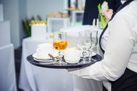 The waiter holding tray with dirty dishes after guests of the event. Catering Service at business meeting, party, weddings. Food Celebration Party Concept. Selective focus, space for text