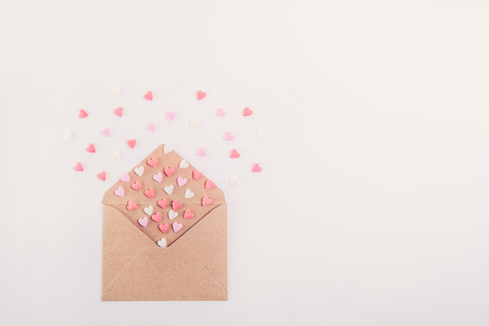 Pink, red and white sweets sugar candy hearts fly out of craft paper envelope on the white background . Valentine day concept. Gift for lover. Selective focus. Space for text