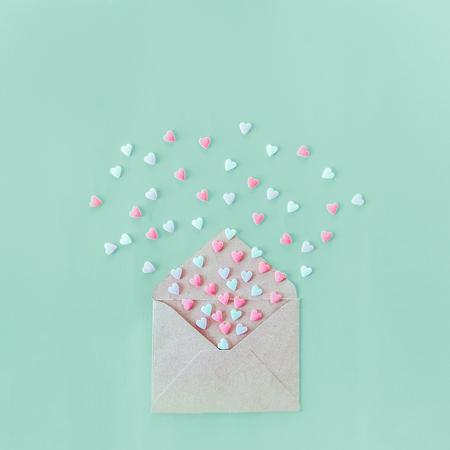 Dulces multicolores corazones de caramelo de azúcar vuelan de sobres de papel artesanal en el fondo turquesa claro. Día de San Valentín. concepto de amor Regalo, mensaje para amante. Espacio para texto. Formato cuadrado