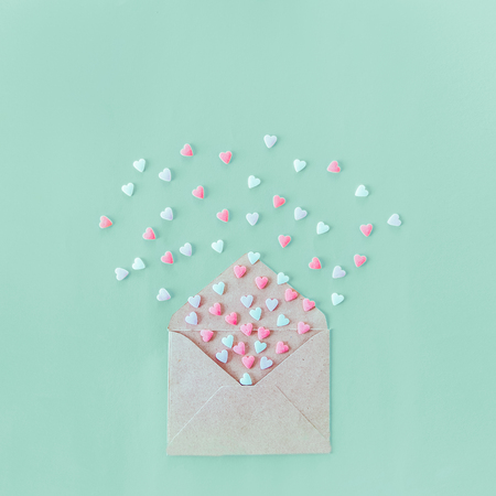 Multicolor sweets sugar candy hearts fly out of craft paper envelope on the light turquoise background . Valentine day. love concept. Gift, message for lover. Space for text. Square format Foto de archivo