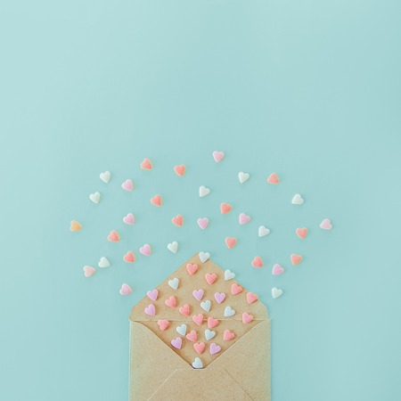 Multicolor sweets sugar candy hearts fly out of craft paper envelope on the light blue background . Valentine day. love concept. Gift, message for lover. Space for text. Square banner Imagens