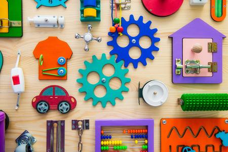 어린이위한 밝은 바쁜 보드를 닫습니다. 어린이 교육 완구. 나무 게임 보드입니다. DIY 간판. 선택적 포커스입니다.