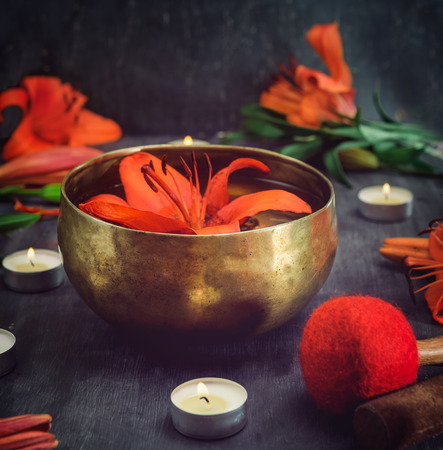 Tibetan singing bowl with floating in water lily inside. Special sticks, burning candles, lily flowers and petals on the black wooden background. Meditation and Relax. Exotic massage. Selective focus
