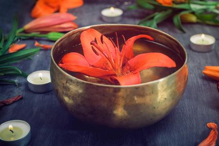 Bol chantant tibétain avec lily flottant à l'intérieur. Brûler des bougies, des fleurs de Lys et des pétales sur le fond en bois noir. Méditation et détente. Massage exotique, procédure de spa. Mise au point sélective Banque d'images