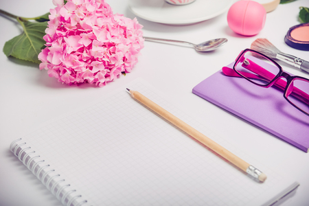 Female hands write To do list on the white working place with female accessories, cup of coffee, notebook, glasses, and wisteria flowers. Fashion background, Beauty blog concept.