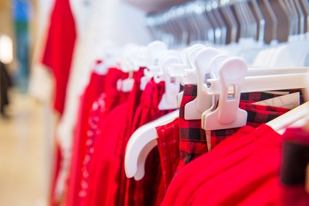 Close up red color Clothes on hangers in shop, butique. Make Outfit set. Shopping Mall. Shopper. Sales. Shopping Center. Selective focus. space for text