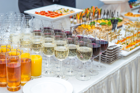 Catering table with alcoholic and non-alcoholic drinks, dishes and snacks food on the event. Service at business meeting, party, weddings. Selective focus, space for text. Stock Photo